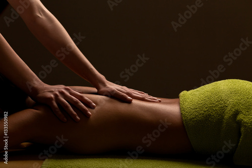 close-up masseur hands doing back massage in spa center. low key Fototapete
