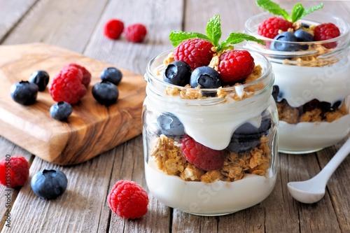 Fototapeta Blueberry and raspberry parfaits in mason jars, scene on a rustic wood background obraz