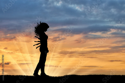 Photo Silhouette of a sad woman with a knives in his back