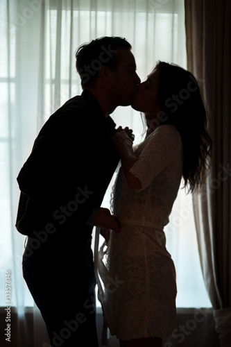 Couple kissing near window. People undressing each other. Ignite the fire of passion. Wall mural