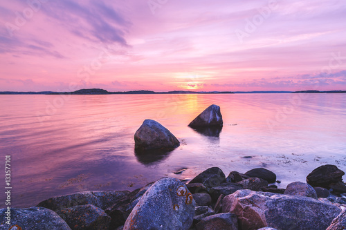 Photo Stands Light pink Violet toning sea shore landscape with great stones at foreground. Location: Sweden, Europe.