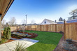 Leinwandbild Motiv Sloped backyard surrounded by wooden fence Luxury New construction home with open floor plan