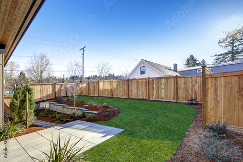Sloped backyard surrounded by wooden fence Luxury New construction home with ope Fototapet