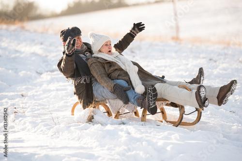 Fotografia  Beautiful senior couple on sledge having fun, winter day.