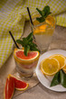 Two glass cups of water with red orange, lemon, mint and ice. Fr