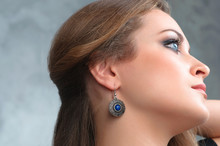 Beautiful Model Brunette With Long Hair And Jewelry Wearing Ear