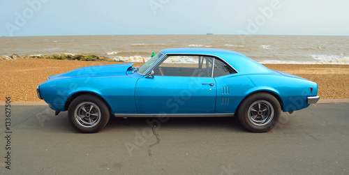 Fotografia Classic Blue motor car  parked on seafront promenade.