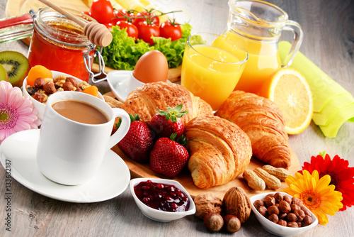 Fototapeta Breakfast consisting of croissants, coffee, fruits, orange juice obraz
