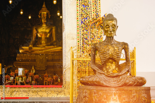 Valokuva  starving Buddha statue with thai art architecture in church Wat Suthat temple