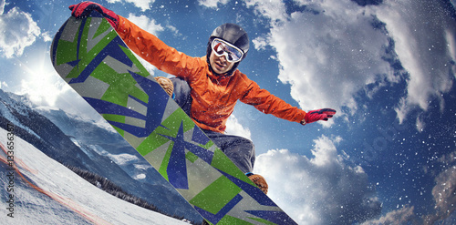 La pose en embrasure Glisse hiver Sport background. Winter sport. Snowboarder jumping through air with deep blue sky in background.
