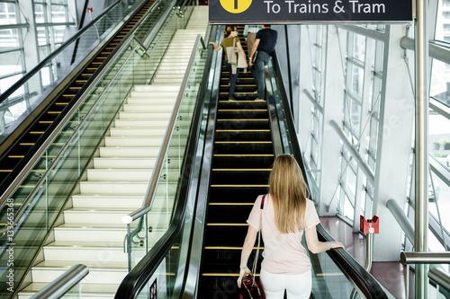 Photo Blonde woman steps on black elevator in skyscraper