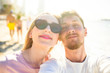 Happy lady in black sunglasses and bearded man pose face to face