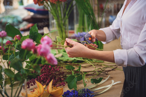 Professional florist cutting flowers in shop