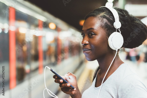 Fényképezés Half length of young beautiful afro black woman traveling on underground, listen
