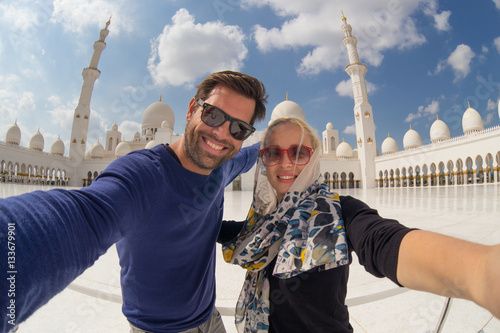 Poster Abou Dabi Tourist couple taking selfie in the courtyard of famous Sheikh Zayed Grand Mosque in Abu Dhabi, United Arab Emirates.