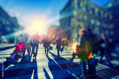 Plakat Sylwetki kolorowych ludzi idących ulicą.