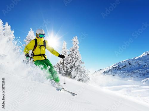 narciarz-w-zoltej-kurtce-zjezdzajacy-w-dol