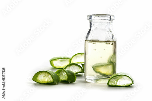 Slices of fresh aloe vera leaf and a bottle with the transparent gel, isolated on white