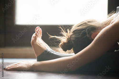 Fotografía  Young woman practicing yoga, sitting in Seated forward bend exercise, paschimott