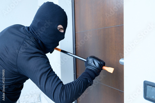 Burglar trying to force a door lock using a crowbar Wallpaper Mural