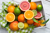 Citrus fruit in wooden tray on white table. Healthy eating and diet.