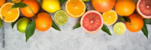 Poster Vruchten Citrus fruit on grey concrete table. Food background. Healthy eating. Long banner format good for web.