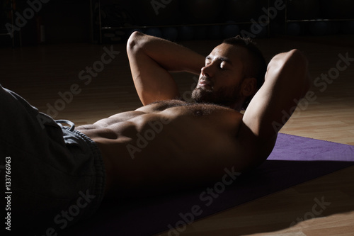Fotografie, Obraz  Fitness model exercising sit ups and crunches. Muscular well bui