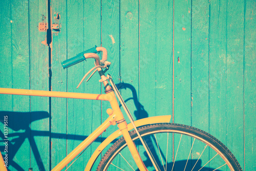 Aluminium Prints Bicycle Yellow old vintage leaning on vintage wall background in the sun.