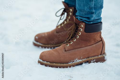 Fotografía  Men's warm winter boots on snow. Brown men's winter boots closeup