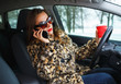 Businesswoman multitasking while driving, drinking coffee and ta
