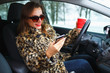 Businesswoman in a fur coat with red lips sending a text message