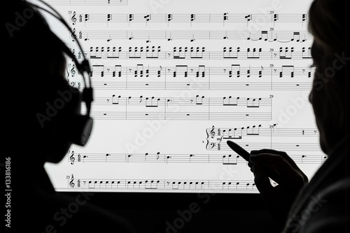 Two people working on a musical score using computer notation software Canvas Print