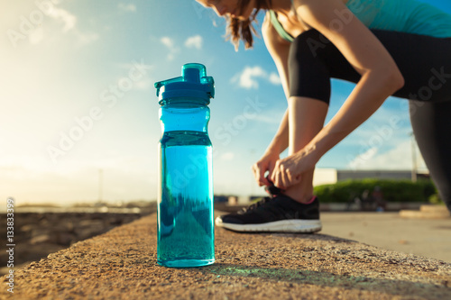 Drinking water concept. Female runner tying her shoe next to bottle of water.