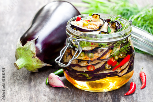 Grilled  sliced eggplant with chili in glass jar on rustic table