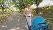 Steadicam shot of happy young woman walking with baby son in stroller at park