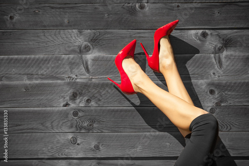 Closeup of woman's sexy legs in red high heels.