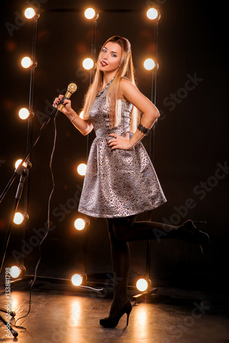 Foto op Plexiglas Wand young smiley beautiful long hair girl with microphone singing song on the stage in karaoke