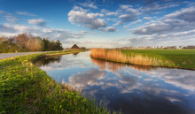 Buildings And Trees Near The Water Canal At Sunrise In Netherlands. Colorful Blue Sky With Clouds. Spring Landscape In Holland. Rural Scene. Cloudy Sky Reflected In Water. Nature Background