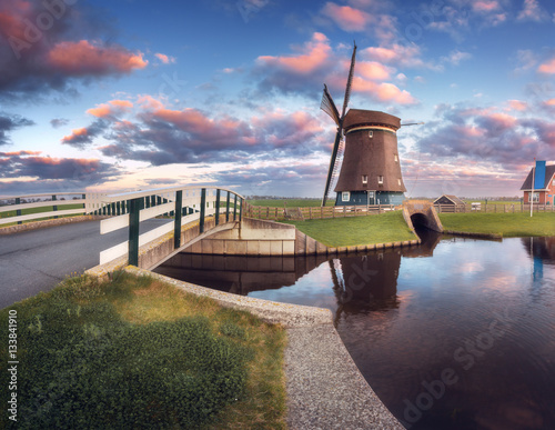 Tuinposter Molens Windmill and bridge near the water canal at sunrise in Netherlands. Beautiful old dutch windmill against colorful sky in dusk. Spring landscape in Holland. Rural scene. Cloudy sky reflected in water
