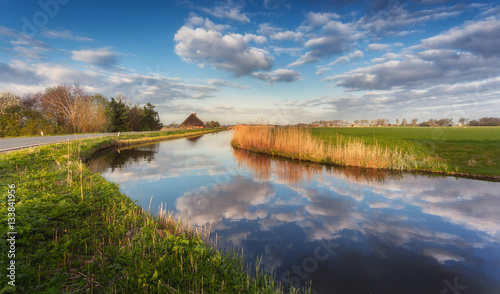 Taupe Buildings and trees near the water canal at sunrise in Netherlands. Colorful blue sky with clouds. Spring landscape in Holland. Rural scene. Cloudy sky reflected in water. Nature background