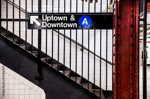 New York City Subway inside and underground with steps and directional sign for Uptown Downtown A train.