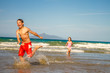 young happy children - boy and girl - having fun on sand beach,