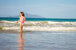 young happy child girl having fun on sand beach, sea background