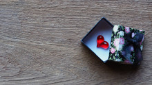 Red Heart Shape In Gift Box Retro Pattern And Black Ribbon On Rustic Wooden Table, Love Concept Background