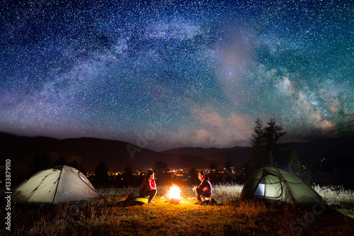 Fototapeta Romantic couple sitting at a campfire near tents in the night under incredibly beautiful starry sky and Milky way. Night camping obraz na płótnie