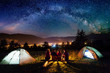 canvas print picture - Friends hikers sitting on a bench made of logs and watching fire together beside camp and tents in the night. On the background beautiful starry sky, mountains and luminous town. Rear view