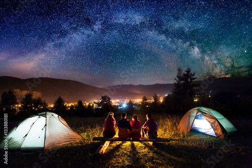 Fotobehang Kamperen Friends hikers sitting on a bench made of logs and watching fire together beside camp and tents in the night. On the background beautiful starry sky, mountains and luminous town. Rear view