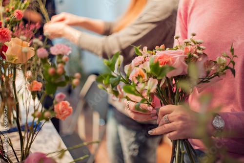 Workshop florist, making bouquets and flower arrangements. Woman collecting a bouquet of roses. Soft focus