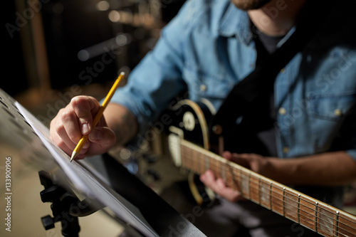 Fotomural  man with guitar writing to music book at studio