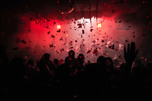 Confetti Fired On Air During A Party In A Disco. Confetti For Background. Silhouette Of Happy People On Dancefloor. Hands Are In The Air
